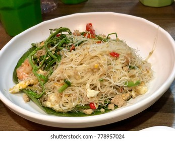 Dried stir fry Asian style spicy noodle with water mimosa and shrimp. Street Food concept.