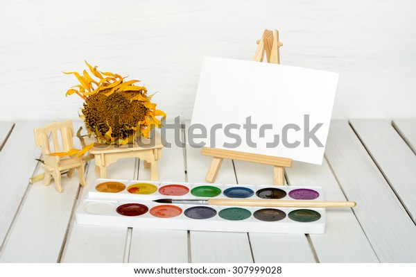 dried sunflower, easel and paints