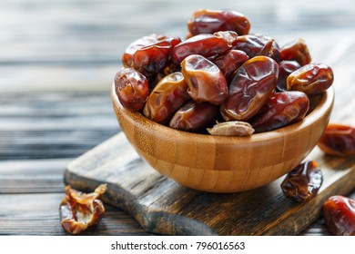 Dried sweet dates in bowl on the old wooden table, selective focus.