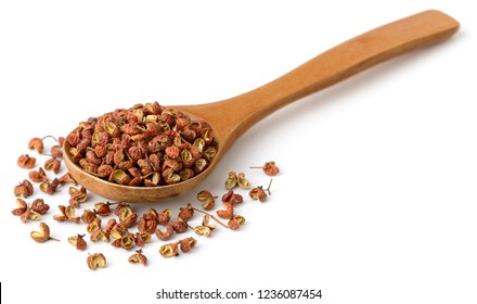 dried Szechuan pepper in the wooden spoon, isolated on the white background