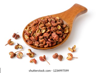 dried Szechuan peppercorns in the wooden spoon, isolated on the white background
