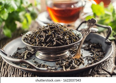 Dried tea leaves in bowl on rustic wooden table.