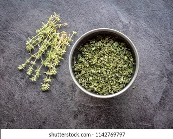 Dried thyme in metal bowl on dark grey table. Overhead shot.