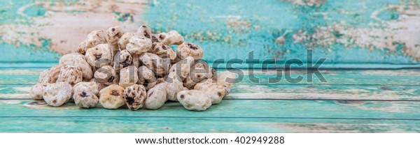 Dried tiger nuts over wooden background