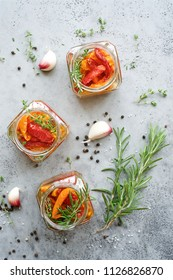 Dried tomatoes preserves with herbs in jar. Gray marble food background