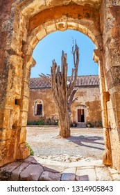 Dried tree behind the arch of old monastery . Arkadi monastery - Crete, Greece.
