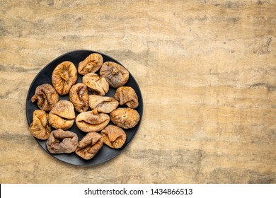 dried Turkish figs on a black plate against textured bark paper with a copy space