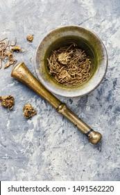 Dried Valerian roots in vintage mortar.Herbal medicine