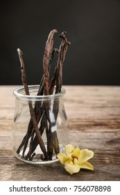 Dried vanilla pods in glass jar and flower on table