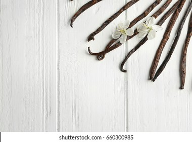 Dried vanilla sticks and flowers on light wooden table