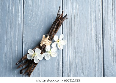 Dried vanilla sticks and flowers on wooden background