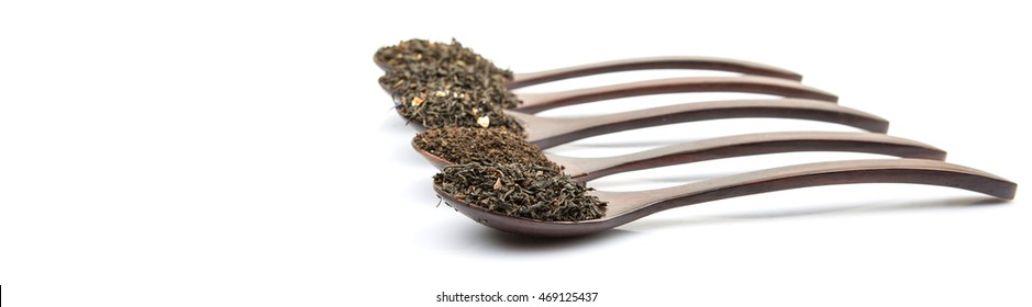 Dried variety of loose black tea leaves in wooden spoon over white background