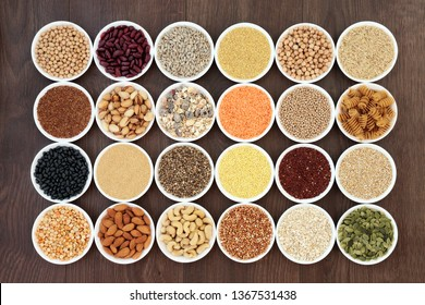 Dried vegan health food with  grains, nuts, seeds, sos mix, cereals, wholegrain pasta and legumes. Super foods high in antioxdants, anthocyanins, protein, vitamins and dietary fibre. Top view on oak.