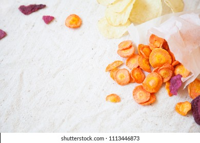 Dried vegetable (carrot, potato, beetroot) chips on linen cloth. Minimal. Copy space.