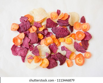 Dried vegetable (carrot, potato, beetroot) chips on paper. Flat lay. Minimal.