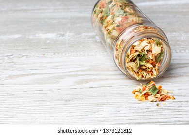 Dried vegetables, on a wooden countertop. Jar with dried vegetables and spices. Spices pouring out of the jar.