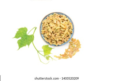 Dried vine fruit of raisins or sultanas in bowl with fresh grape leaves isolated on white background,top view studio shot
