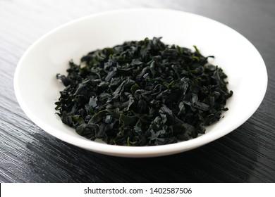 Dried wakame seaweed on black background.