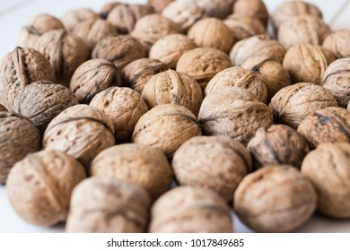 Dried walnuts on wooden white table. Rw, vegan, vegetarian food concept.