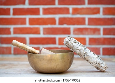 Dried white sage smudge stick and ancient hand crafted traditional Tibetan meditation and healing singing bowls made from 7 sacred metals which are typical accessories used in buddhism, yoga and