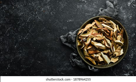dried wild organic porcini mushroom on a black stone background. Autumn food. Top view. Free space for text.
