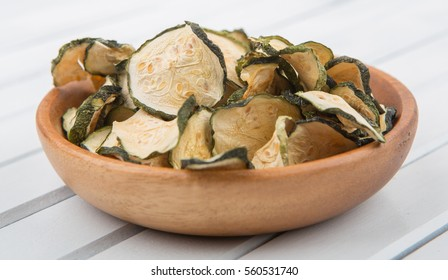 Dried zucchini in a wood bowl on wooden background