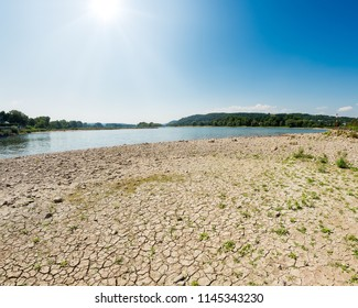 Dried-out riverbed with stones and sediments in the river Rhine with low water level between groins on a sunny day, caused by prolonged drought, North Rhine-Westphalia, Germany, Europe