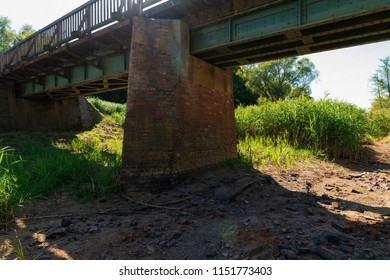 Dried-up riverbed under a bridge during a heat wave