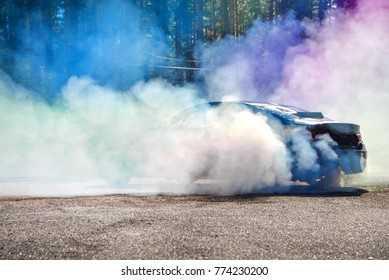 Drift car warming up the tires before  start, waiting for race to begin. Blue and purple smoke all around.