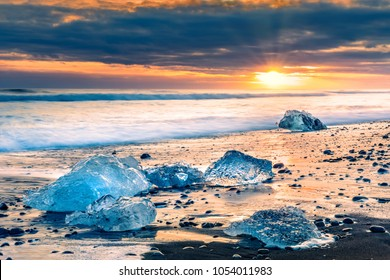 Drifting ice blocks on Diamond beach, at sunset, in Jokulsarlon, Iceland
