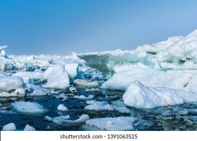 Drifting ice in the sea near the sandy coast. Ice in the sea near the beach