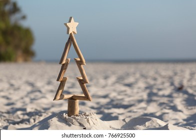A driftwood Christmas tree in the sand on the beach in summer