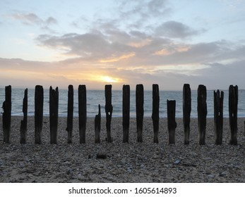 Driftwood and old fence on a pebble beach in Southsea, Hampshire, England, UK. Sea behind is the Solent. Isle of Wight is visible in the background. Taken from Portsmouth.