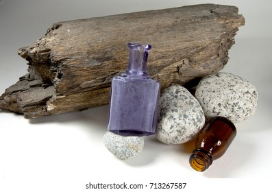 Driftwood and river rock along with antique purple and brown bottles on a white background