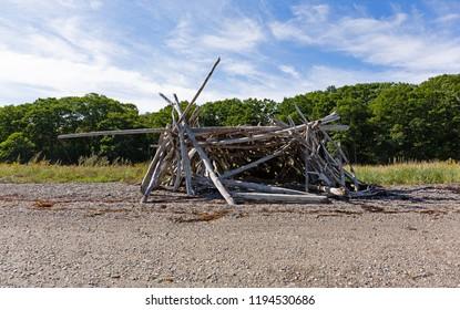 Driftwood sticks arranged in a haphazard lean to on a beach in Maine.