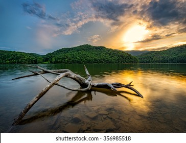 Driftwood at sunset reflects in the calm waters of this Appalachian Mountain lake in Kentucky