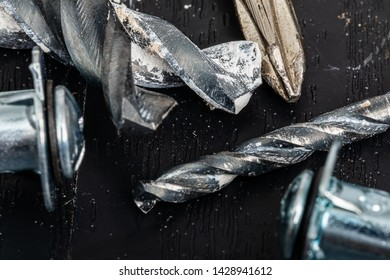 Drill Bits, Screw Drivers and Anchor Screws together in a tight macro image.  the dirty drillbit is the primary focus subject at center frame.