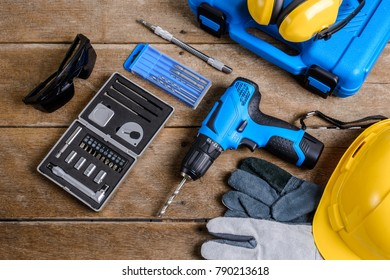 Drill and set of drill,tools,carpenter and safety, Protection Equipment on wooden table background