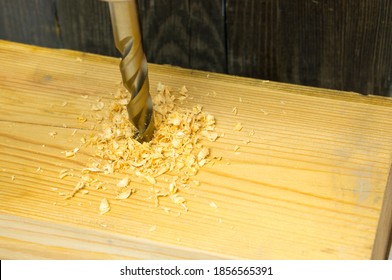 A drill for woodworking punches a hole in a wooden block with a lot of wood chips. Wood shavings from a drill.