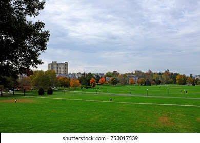 Drillfield view at Virginia Tech during fall with maroon and orange colored trees in the background, Blacksburg, Virginia, USA