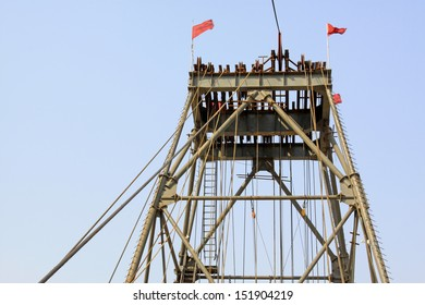 drilling derrick in a iron mine in the blue sky