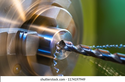 Drilling detail on a lathe with metal shavings. Close-up of a metallic workpiece clamped in a rotating machine chuck. Steel drill bit and twisted swarfes on a green background. Beautiful motion blur.