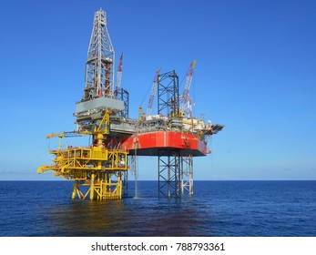 Drilling jack up rig on oil well platform with blue sky background in offshore oil field