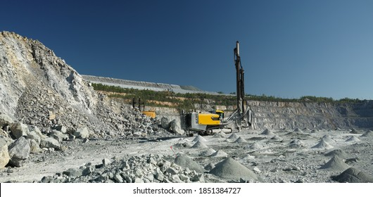 Drilling machine on the background of rocks and stony relief of a shale quarry and a blue sky, panorama.