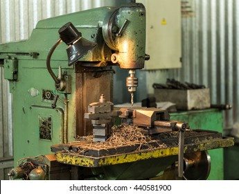 Drilling machine in operation, revolves the spindle, the machine studded with steel shavings. A few finished parts in the frame