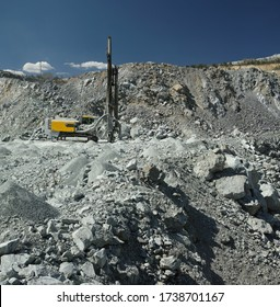 Drilling machine works in a quarry against the background of placer shale ore and blue sky, in sunny weather, panorama. Mining machinery.