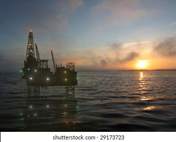 the drilling platform on sea on background of the setting sun
