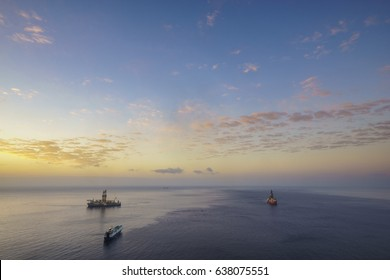 Drilling platforms in the ocean at sunrise, view from the air