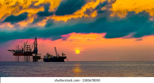 Drilling rig and FPSO ship silhouette view with sunset golden hours sky in landscape beautiful view