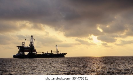 Drilling rig with FPSO ship at site in the evening golden hours.